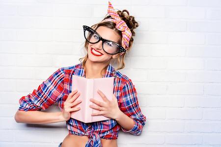 Lustige glamouröse Pin-up-Mädchen im eleganten riesigen Gläsern ein Buch lesend. Standard-Bild - 47282933