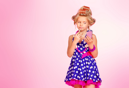 Cute little girl playing with her mothers cosmetics. Kids fashion, cosmetics. Pin-up style.