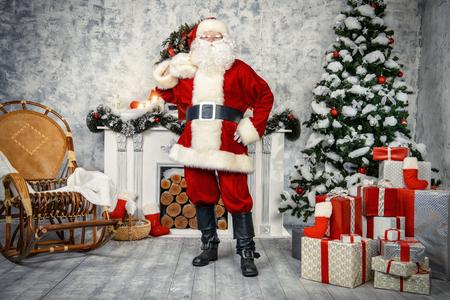 Tradizionale Babbo Natale in piedi accanto al camino e albero di Natale in una bella stanza, decorato per Natale. Archivio Fotografico - 47552039