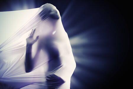 女性のシルエットが黒の背景に白い布を突破します。アート プロジェクト、劇場。モダン ・ ダンス。 写真素材