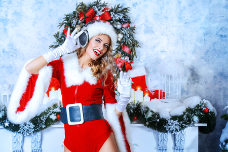 Beautiful young woman in Santa Claus costume and headphones over Christmas background. Christmas party, DJ girl.