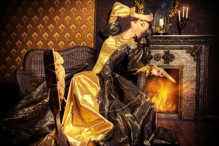 美しい緑豊かなドレスで白雪のような美しい妖精の女の子は糸車の回転します。 ルネッサンス。バロッコ。ファッション。おとぎ話。