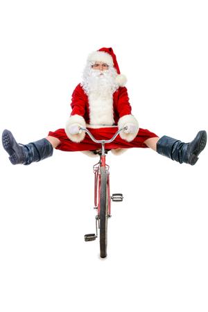 アクティブな陽気なサンタ クロース彼の自転車でポーズします。白い背景に分離されました。 写真素材
