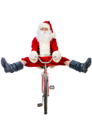 Active jolly Santa Claus posing with his bicycle. Isolated over white background.