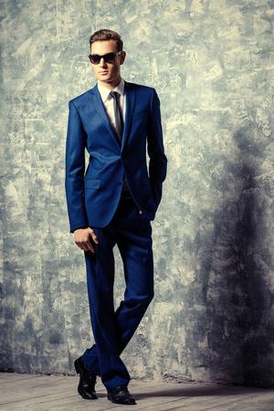 Retrato de cuerpo entero de un hombre joven y guapo de moda en elegante traje clásico y gafas de sol.