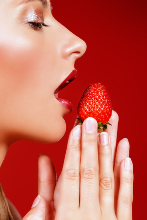 Close-up of a young woman eating fresh strawberry.