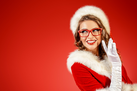 Sexy young woman in Santa costume and elegant red glasses. Red background. Christmas celebration.