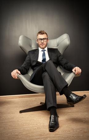 Imposante volwassen man in een elegante pak zittend op een leren stoel in een moderne luxe interieur. Stockfoto