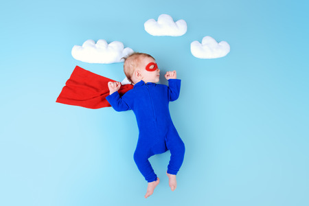 Newborn baby. Little super hero flying through the sky. Фото со стока