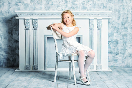 Elegant eight-year girl in white dress stands by the old vintage fireplace. Kids fashion.