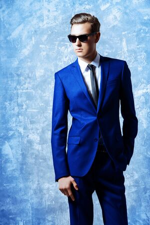 Fashion shot of a handsome young man in elegant classic suit and sunglasses. Reklamní fotografie