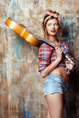 Pretty pin-up girl posing with guitar. Beauty, fashion. Фото со стока
