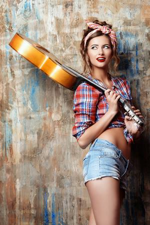 Pretty pin-up meisje stellen met gitaar. Schoonheid, mode.