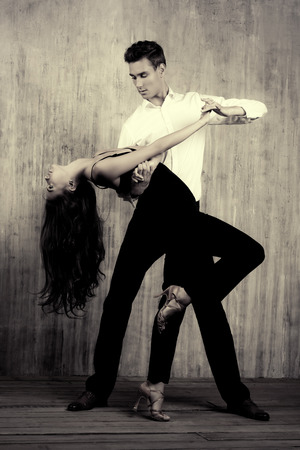 Black-and-white portrait of a beautiful young couple dancing tango with passion. Professional dancers. Latino dancers.