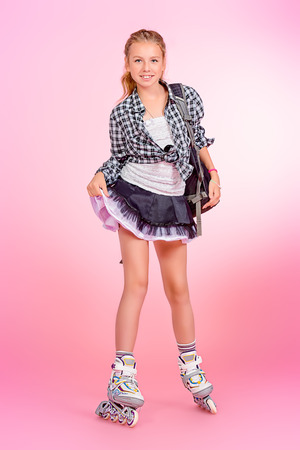 Full length portrait of a modern teen girl in roller skates posing over pink background.