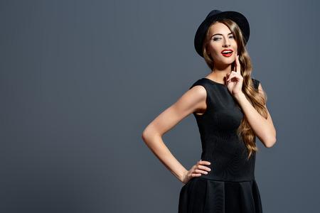 Joyful hübsches Mädchen mit schwarzen Kleid und schwarzen klassischen Hut Lächeln in die Kamera. Beauty, Fashion-Konzept. Hipster-Stil. Standard-Bild
