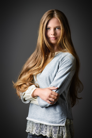 Pretty teenager girl in casual clothes posing over grey background. Modern teen generation. Youth fashion.