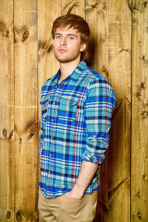 Portrait of a handsome young man in casual shirt standing by a wooden wall. Mens beauty, fashion.