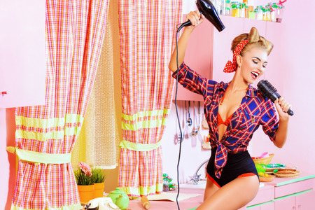 Beautiful pin-up girl doing a hair with a hair dryer and comb on her pink kitchen. Retro style. Fashion.
