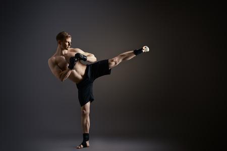 キックを実行するスポーツウェアの人。総合格闘技。スタジオ撮影します。