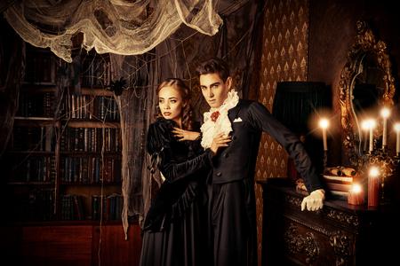 Piękne wampiry mężczyzna i kobieta ubrani w średniowieczne ubrania stoją w pokoju w starym opuszczonym zamku. Halloween.