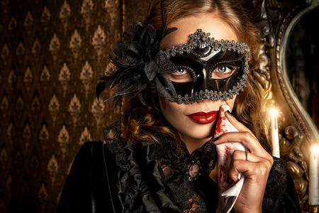 Charmante mysterieuze meisje in zwart masker en zwarte middeleeuwse jurk staat in een kasteel woonkamer. Vampier. Halloween concept. Vintage stijl.