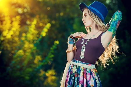 Boho stijl mode. Mooie jonge vrouw die boho-stijl kleren poseren in de stralen van de avondzon, zonsondergang. Stockfoto