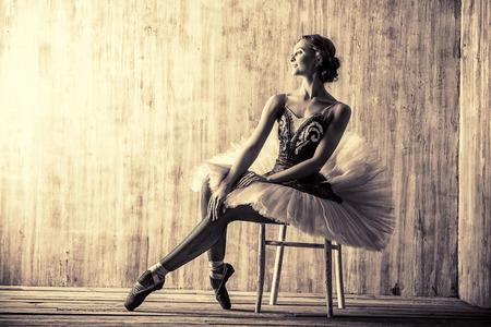 Professional ballet dancer posing at studio over grunge background. Art concept. Toned photo, vintage style.
