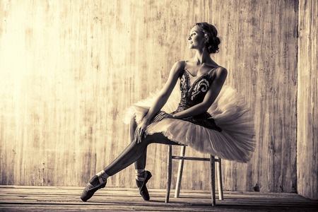 Professional ballet dancer posing at studio over grunge background. Art concept. Toned photo, vintage style.