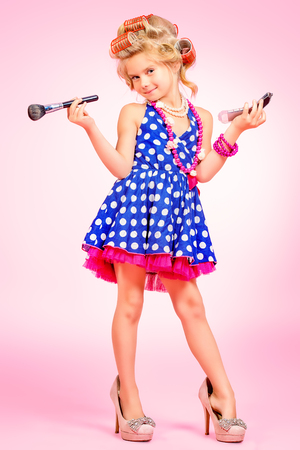 Mooi meisje in de schoenen van haar moeder en haar krulspelden. Kid's mode, cosmetica. Pin-up stijl.