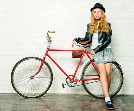 Modern girl teenager stands with her old bicycle by a brick wall.