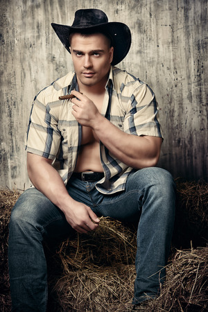 Reizvoller Cowboy auf einem Heuhaufen. Western-Stil.