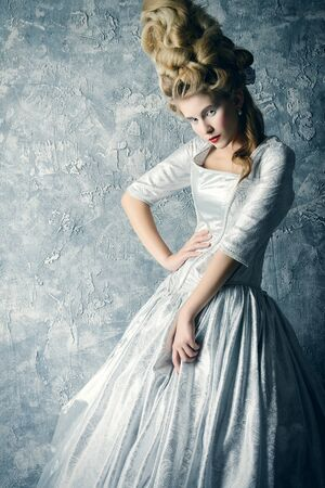 Beautiful young lady in a historical dress and high hairdo in a Renaissance style. Vintage fashion. Elegant Ice Queen over frozen background..