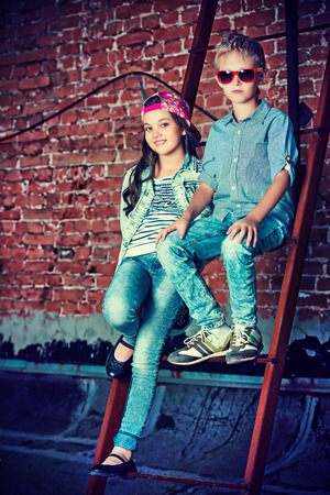 Modern children wearing casual jeans clothes posing on the city street by a brick wall. Kids fashion.