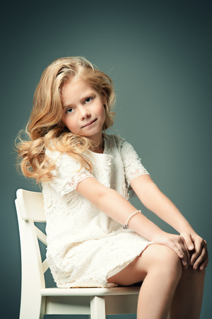 Fashion shot of a pretty little girl with beautiful blonde hair wearing white dress. Studio shot. Kids beauty, fashion.