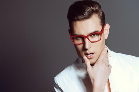 Moderne jonge man in witte jas en elegante rode bril. Studio fashion schot. Optiek. Stockfoto