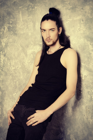 Un alto, magro uomo bruna posa dalla parete del grunge. Bellezza maschile, la moda.