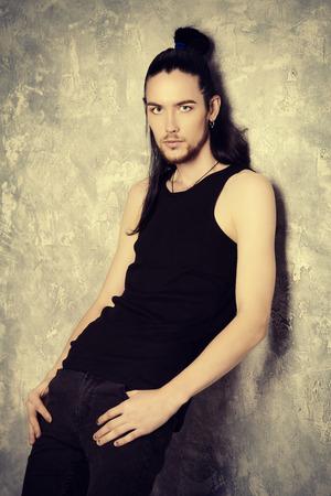Un grand, mince homme brune posant par la paroi du grunge. La beauté des hommes, la mode.