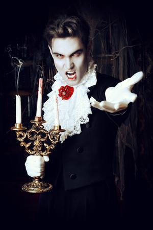 Handsome Vampir Mann mit eleganten Frack steht in der alten mittelalterlichen Burg. Halloween.