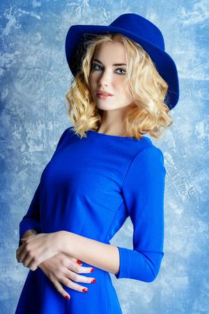 青いドレスとエレガントな帽子を身に着けている美しいブロンドの女の子のファッションの肖像画。