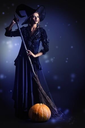 Gorgeous brunette witch with her broom over black background. Halloween.