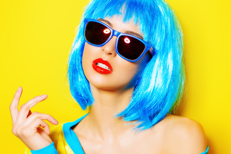 Lumineux fille glamour dans des vêtements vives et une séduisante de perruque sur fond jaune. Beauté, mode. Cosmétiques, hairtsyle. Optique, lunettes.
