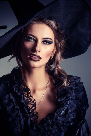 Portrait of a gorgeous brunette witch in black dress and a hat over black background. Halloween.