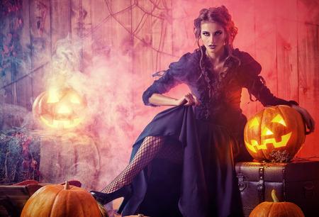 Scary aantrekkelijke heks in een verlaten houten huis in bloedrode mist. Halloween. Stockfoto