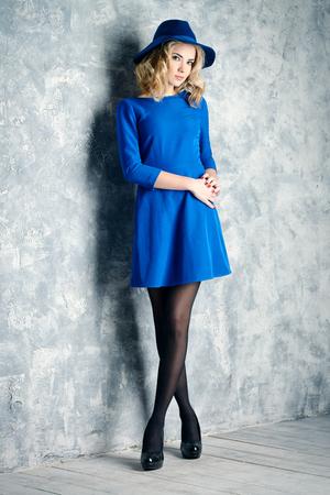 Full length fashion portrait of a beautiful blonde girl wearing blue dress and elegant hat.