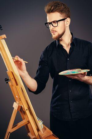 Homme artiste peint sur un chevalet à l'atelier. Occupation.
