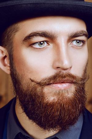 エレガントな男ひげと口ひげのスーツと山高帽帽子をかぶっています。古いスタイルのファッション。