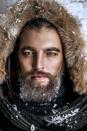 ひげと口ひげの冬の服を着てハンサムな残忍な男の肖像は霜で覆われています。