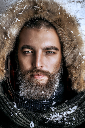 Portrait of a handsome brutal man with beard and mustache dressed in winter clothes, covered with frost. Stockfoto