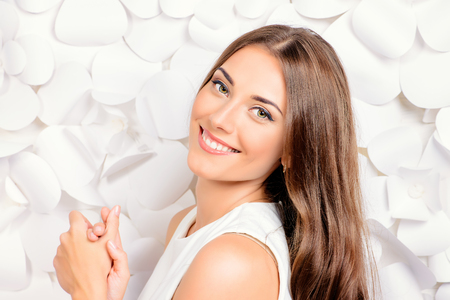 Smiling young woman in white dress posing by the background of white paper flowers. Beauty, fashion. Healthy teeth. Cosmetics. Reklamní fotografie - 52480844